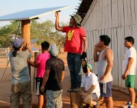 Men from the Xingu Indigenous Park install a solar panel in the village of Pyulaga.