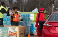Volunteers distribute bottled water and fresh food to residents at one of the city's HELP centers.