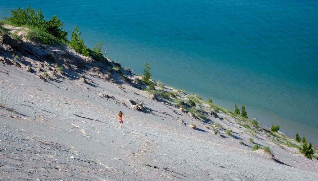 A girl runs down the face of a massive dune known as Old Baldy.