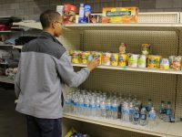 A teenager organizes cans of donated food on the shelves of a food pantry.