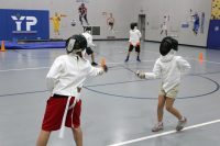 Two young students standing in a gym wearing full fencing gear clash swords.