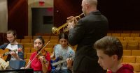 A group of musicians play guitar, violin and trumpet.