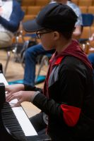 A young student plays piano.