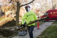 A construction worker in Flint carries away an old galvanized water pipe that will be replaced.