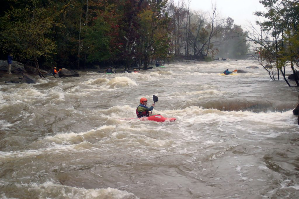 The image shows the Great Falls on the Catawba River in South Carolina at full flow with kayakers enjoying the challenging rapids of the full flowing river. ubber boots looking around and talking.