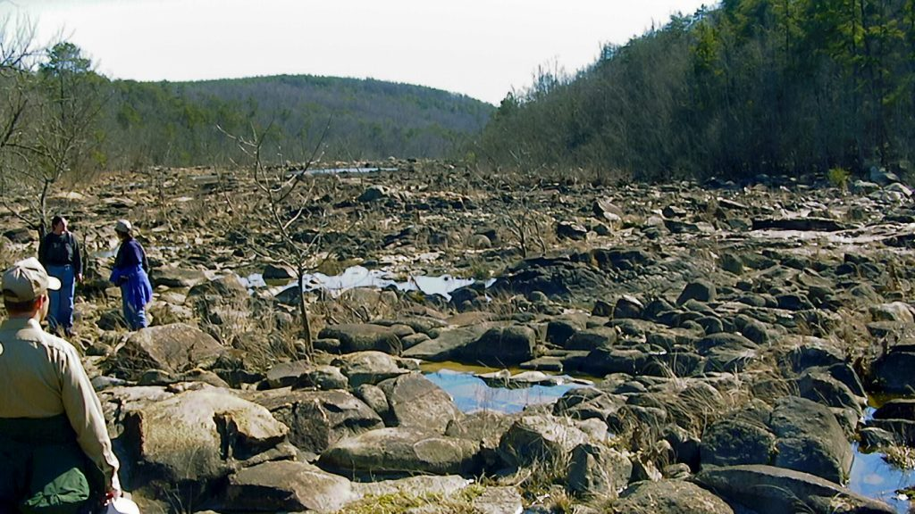 The image shows the dry river bed of Great Falls on the Catawba River in South Carolina with large boulders and people with rubber boots looking around and talking.