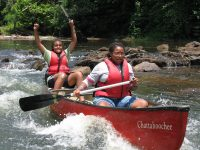 Two young women are paddling a canoe through smaller river rapids and in between large boulders.