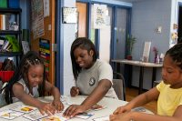 AmeriCorps member Jani Toney sits at a table with two young students as they work on flashcards with synonyms.