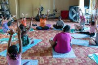 Young girls sit on yoga mats while watching and following instructions given to them by the yoga teacher as she demonstrates in front of the class.