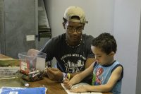 Young adult helps a younger boy with coloring activities at the Berston Filed House in Flint, Michigan on July