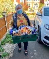 A volunteer woman wears a protective face mask and stands with a basketfull of items that will be deivered to people that are in need of assistance with getting food and other household items during the coronavirus pandemic.