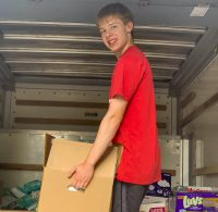Young man in the back of a small cargo truck loads in baby diapers to be distributed in the area.